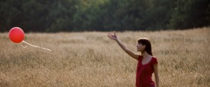 A young woman standing in a field letting go of a red balloon